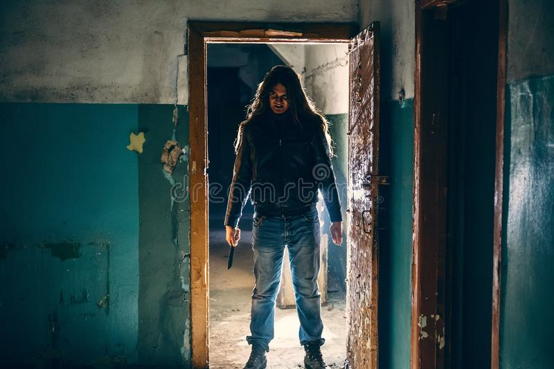 Silhouette of criminal or maniac with knife in hand in old scary building, serial killer with cold weapon royalty free stock image