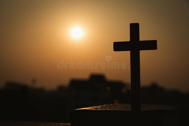 Silhouette of cross and bible with the sunset as background, christian concept, spirituality and religion royalty free stock photo