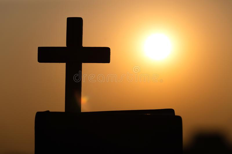 Silhouette of the cross on the holy bible, religion symbol in light and landscape over a sunrise, background, religious, faith. Concept stock image