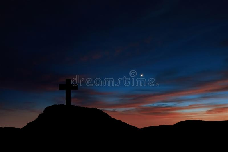 Silhouette of a cross on the mountain at sunrise stock images