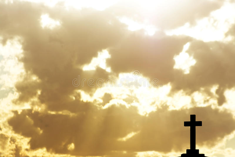 Silhouette of a cross over glowing clouds stock photos