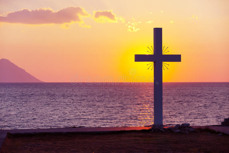 Silhouette of cross at sunrise or sunset with light rays and sea panorama. Greece royalty free stock photos