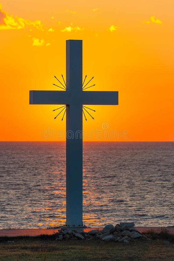 Silhouette of cross at sunrise or sunset with light rays and sea panorama. Greece stock photography