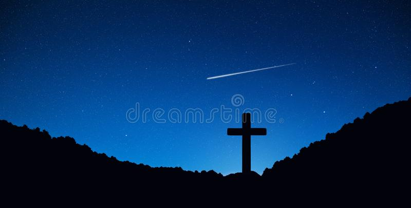 Silhouette of crucifix cross on mountain at night time with star and space background. stock photo