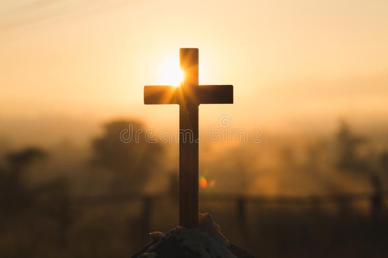 Silhouette of crucifix cross at sunset time with holy and light background.  stock images