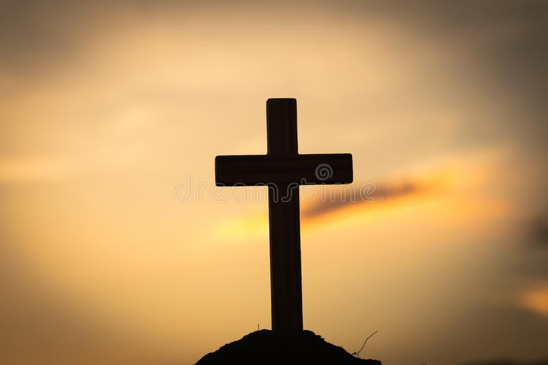 Silhouette of crucifix cross at sunset time with holy and light background.  royalty free stock photos