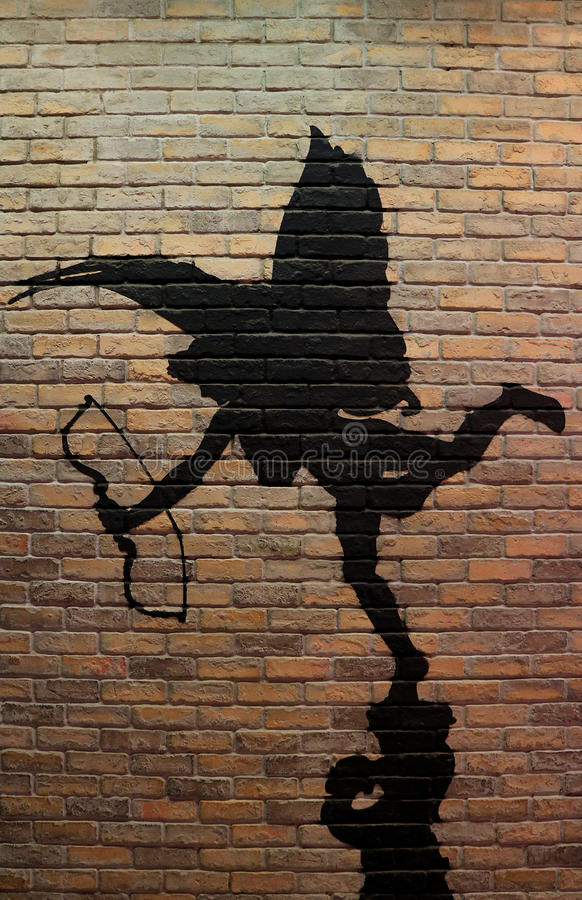 Silhouette of cupid painting on the bricked wall, vertical photo stock photography