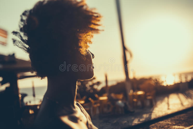 Silhouette of curly brazilian girl on sunset stock photo