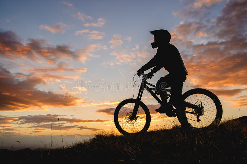 Silhouette of a cyclist rider on a sports bicycle against the backdrop of the setting sun in the mountains royalty free stock images
