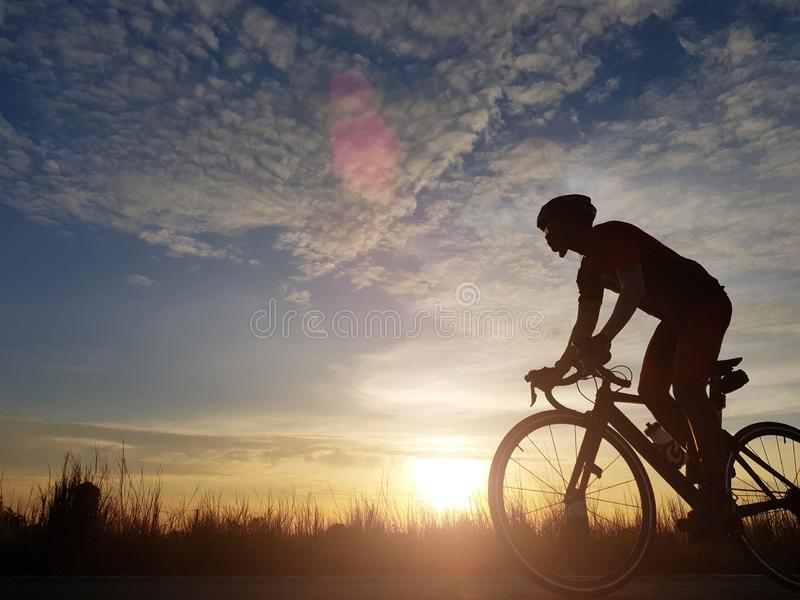 Silhouette of cyclist riding a road bike on open road in evening during sunset. Sports and outdoor activities concept.  stock images