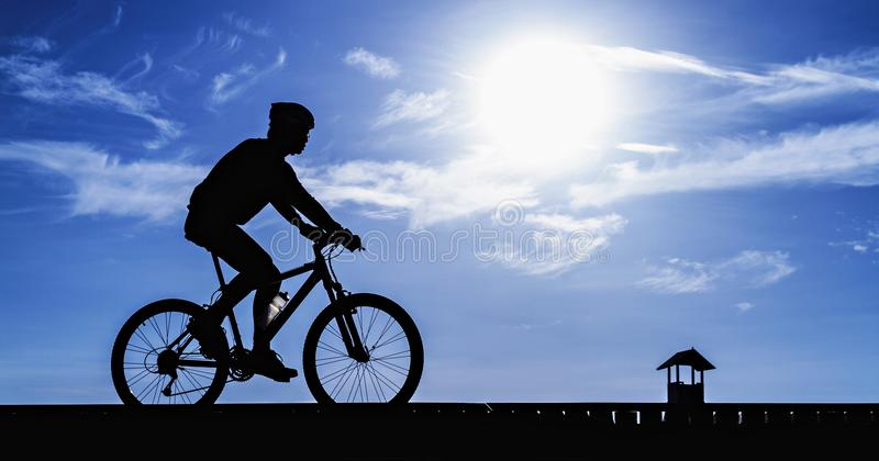 Silhouette of the cyclist riding a road bike. At sunset royalty free stock images