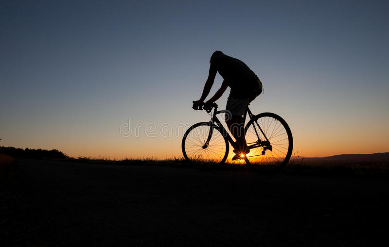 Silhouette of cyclist in sunset. With race bike royalty free stock photography