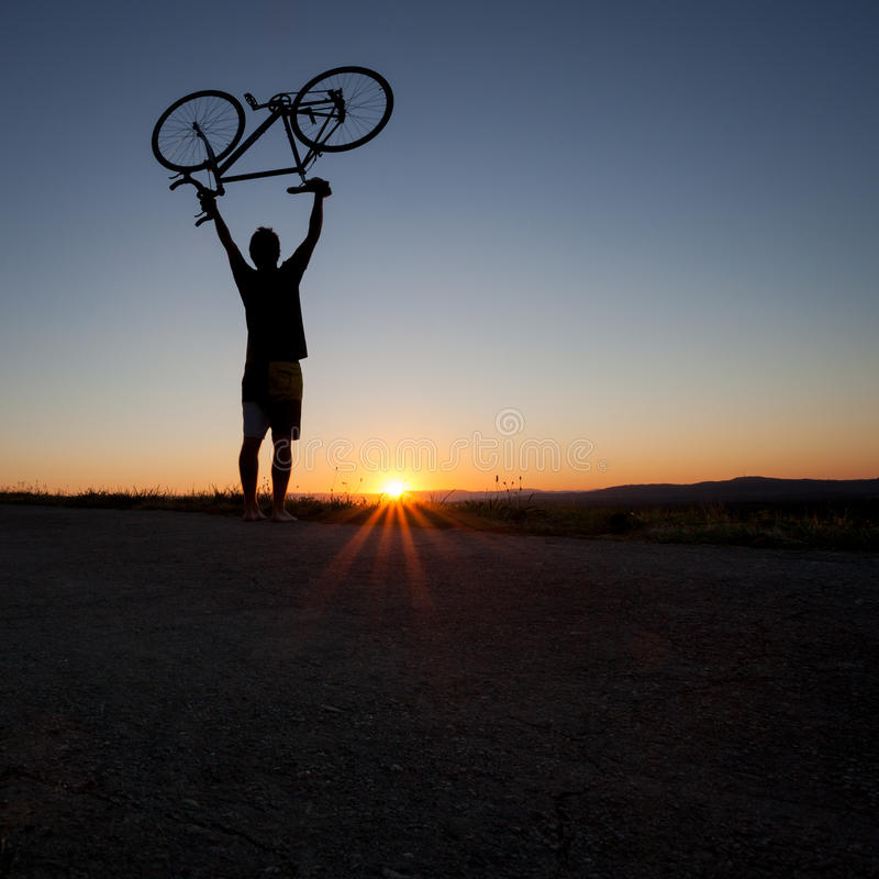 Silhouette of cyclist in sunset. On road stock photo