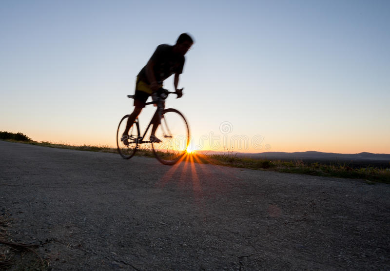 Silhouette of cyclist in sunset. On road stock photos