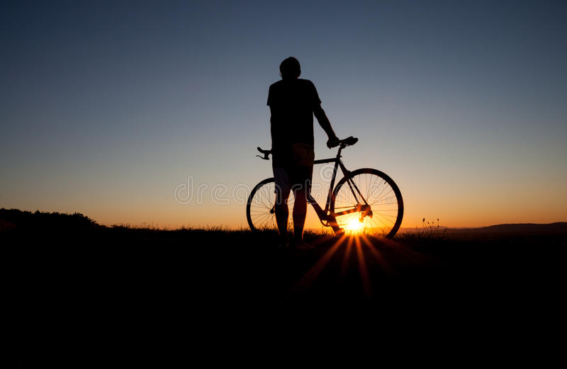 Silhouette of cyclist. In sunset sky royalty free stock photo