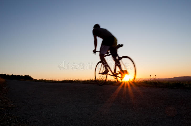 Silhouette of cyclist. In sunset sky stock image