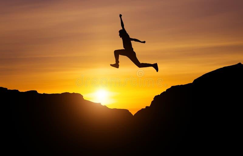 Silhouette d'athlète, sautant par-dessus des roches dans le secteur de montagne image libre de droits