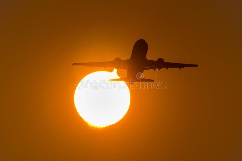 Silhouette d'avion décollant pendant le coucher du soleil, mouches par le disque du soleil photos libres de droits