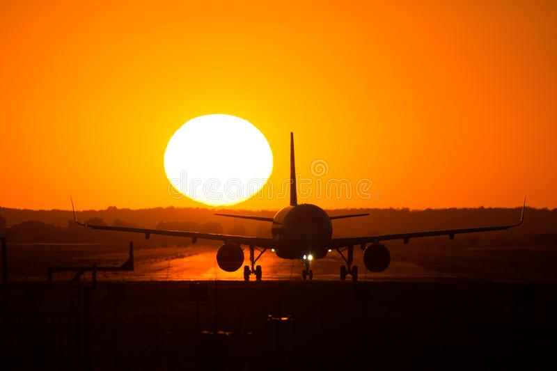 Silhouette d'avion sur le coucher du soleil, après le débarquement photo libre de droits
