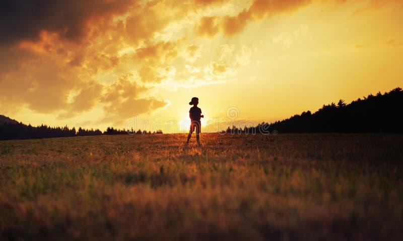 Silhouette d'enfant heureux jouant sur le pré au coucher du soleil photos libres de droits