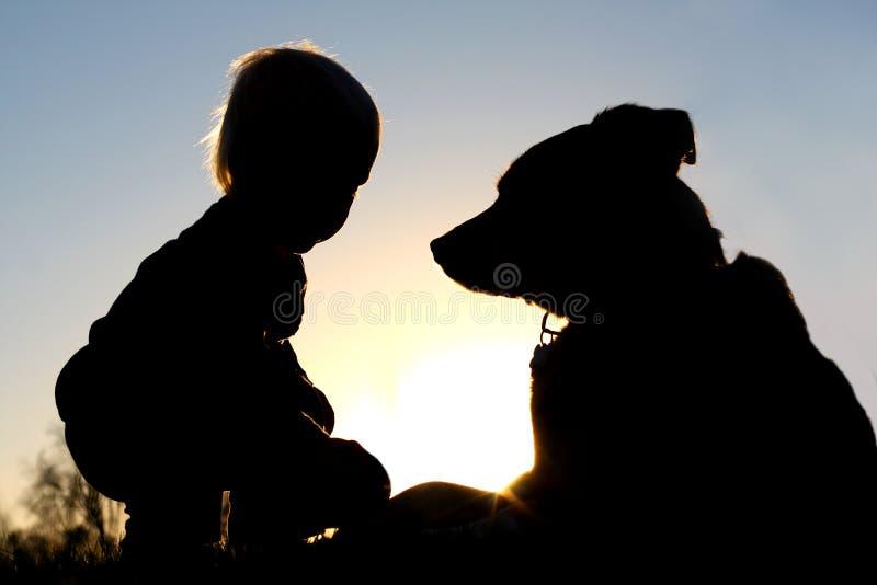 Silhouette d'enfant jouant avec le chien photos stock