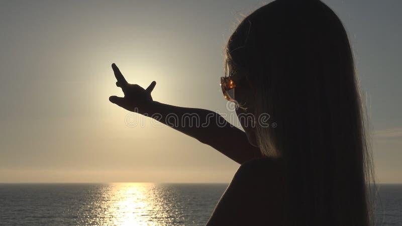 Silhouette d'enfant jouant sur la plage, enfant dans le coucher du soleil, main de fille dans des rayons de Sun, poutre photographie stock