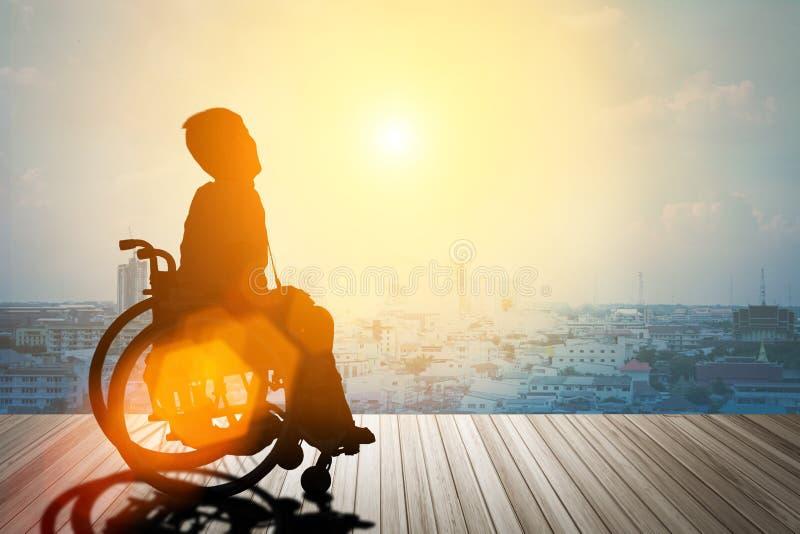 Silhouette d'handicapé sur le fauteuil roulant photo libre de droits
