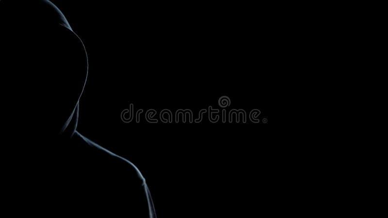 Silhouette d'homme à capuchon sur le fond noir, calibre pour la statistique de crime photo libre de droits