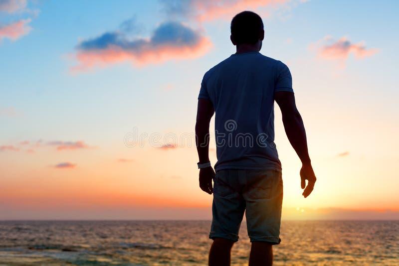 Silhouette d'homme au coucher du soleil près de la mer photographie stock libre de droits