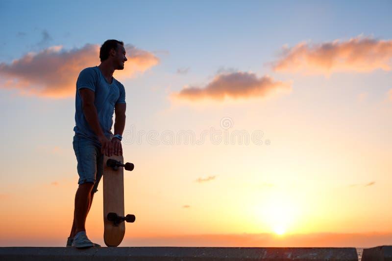 Silhouette d'homme avec la planche à roulettes près de l'océan photographie stock