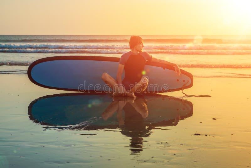 Silhouette d'homme de ressac se reposant avec une planche de surf sur la plage de bord de la mer au temps de coucher du soleil photos stock