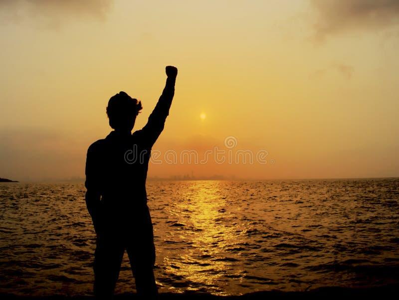 Silhouette d'homme gai soulevant des mains pendant le coucher du soleil au-dessus de la mer Concept réussi image stock