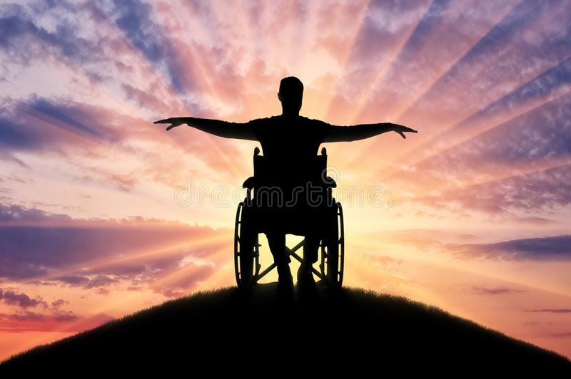 Silhouette d'homme handicapé heureux dans le fauteuil roulant sur la colline photographie stock