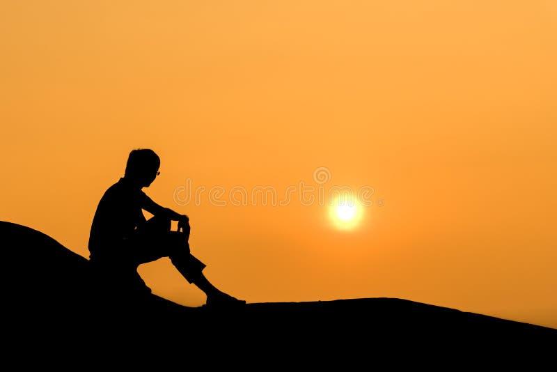 Silhouette d'homme s'asseyant sur la roche au coucher du soleil images stock