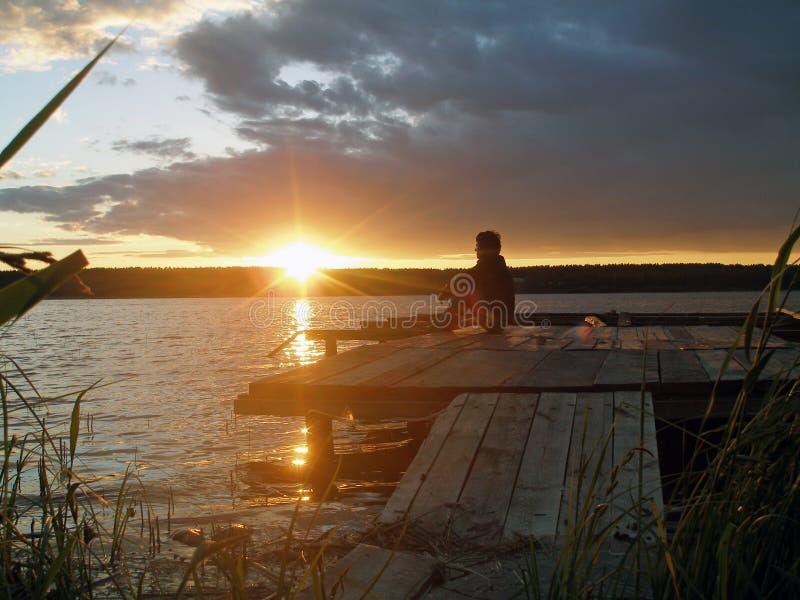 Silhouette d'homme triste seul au coucher du soleil photographie stock