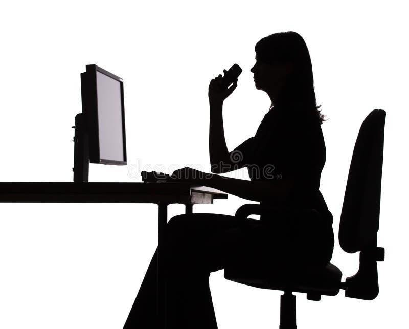 Silhouette d'ordinateur fonctionnant de femme (téléphone) photo libre de droits