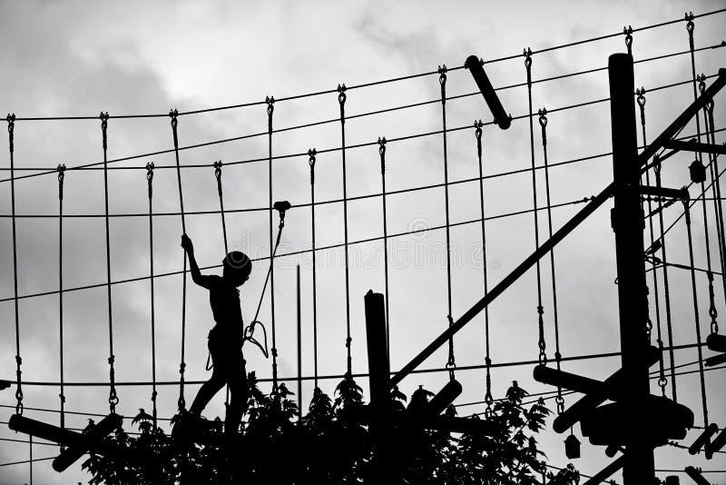 Silhouette d'un adolescent s'élevant sur la ligne de fermeture éclair et essayant de trouver son équilibre image libre de droits