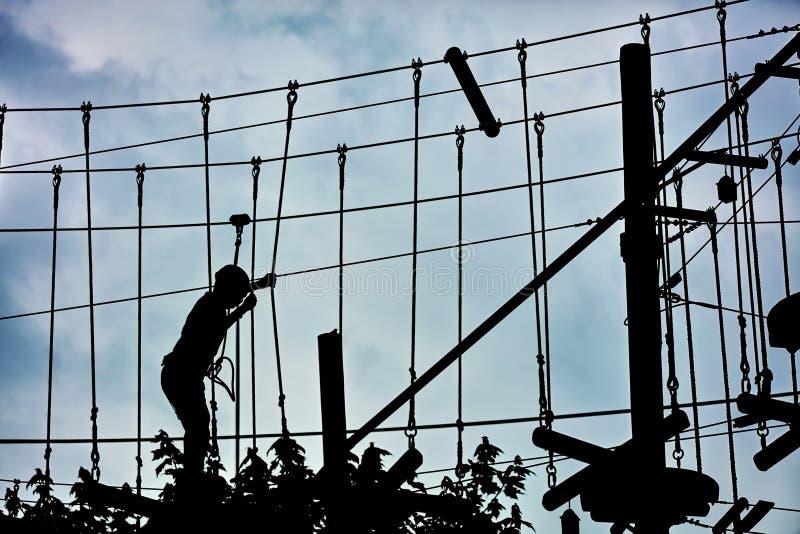 Silhouette d'un adolescent s'élevant sur la ligne de fermeture éclair et essayant de trouver son équilibre images libres de droits