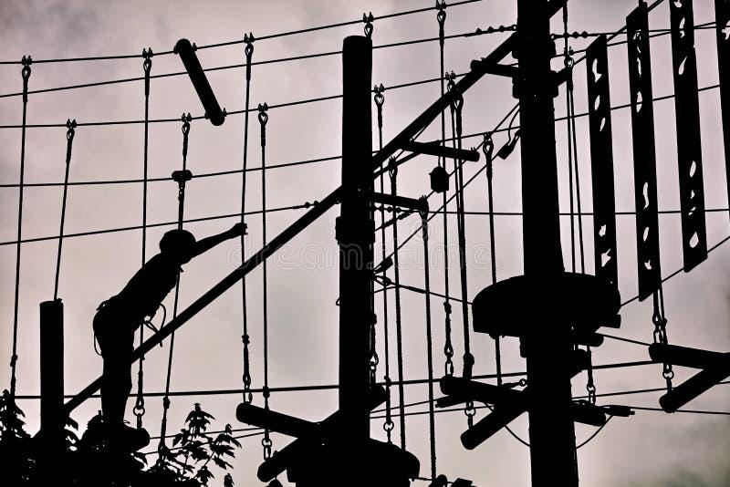 Silhouette d'un adolescent s'élevant sur la ligne de fermeture éclair et essayant de trouver son équilibre sur le fond de ciel nu photo libre de droits