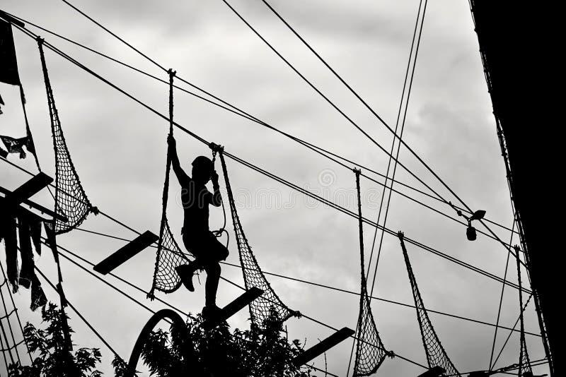 Silhouette d'un adolescent s'élevant sur la ligne de fermeture éclair et essayant de trouver son équilibre sur le fond de ciel nu image stock