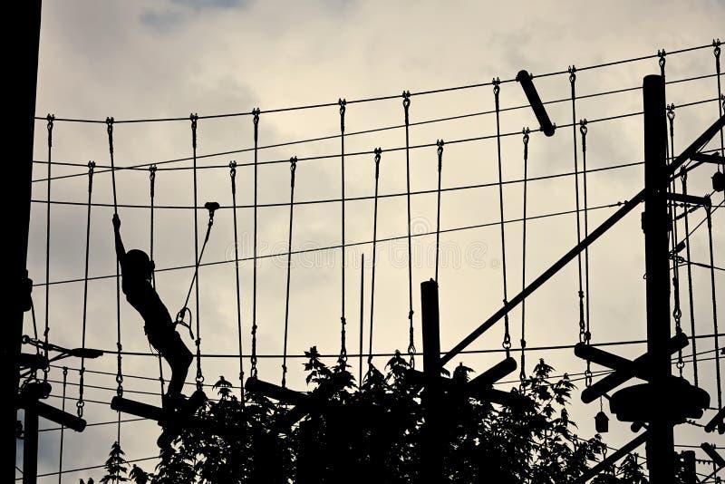 Silhouette d'un adolescent s'élevant sur la ligne de fermeture éclair et essayant de trouver son équilibre photo libre de droits