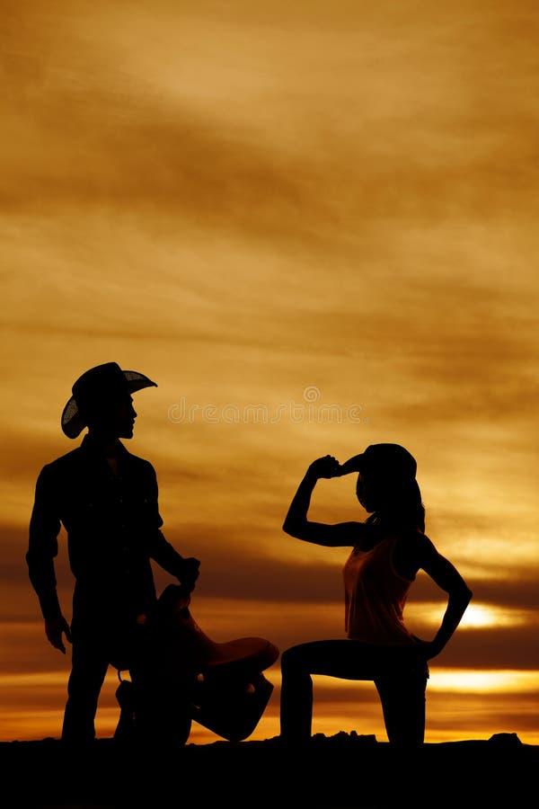 Silhouette d'un agenouillement de cow-girl sur une main de genou sur le chapeau photographie stock
