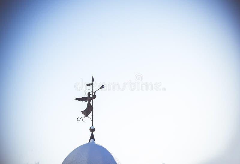 Silhouette d'un ange Weathervane sur le dôme du temple contre le ciel bleu propre Le concept de la paix et de la religion photos stock