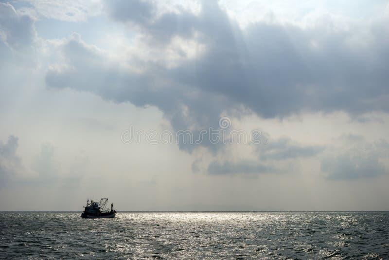 Silhouette d'un bateau de pêche en mer photo libre de droits