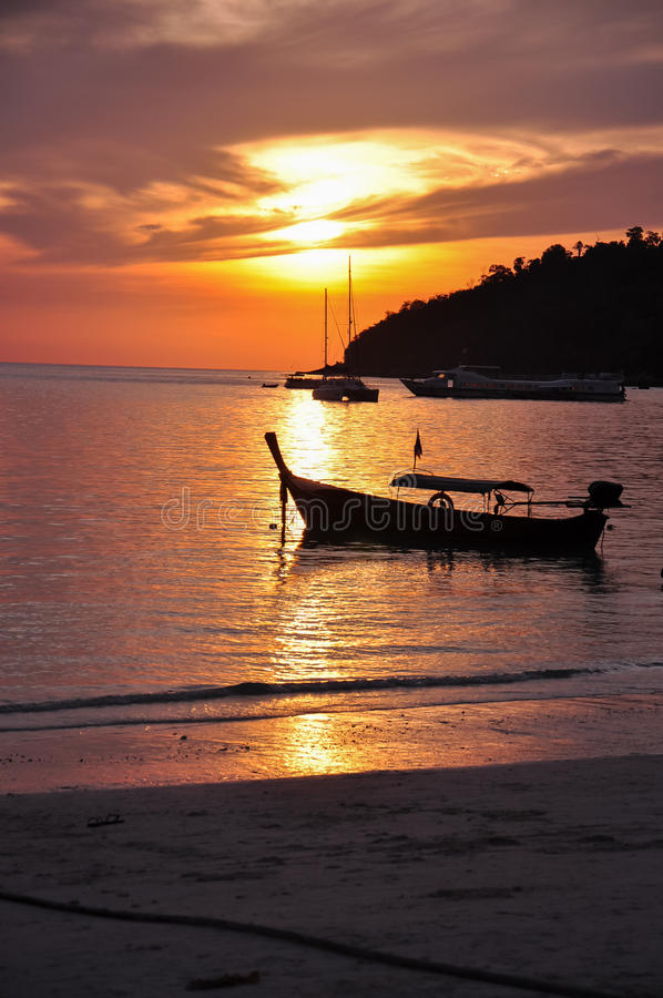 Silhouette d'un bateau flottant sur une mer pendant le coucher du soleil images libres de droits