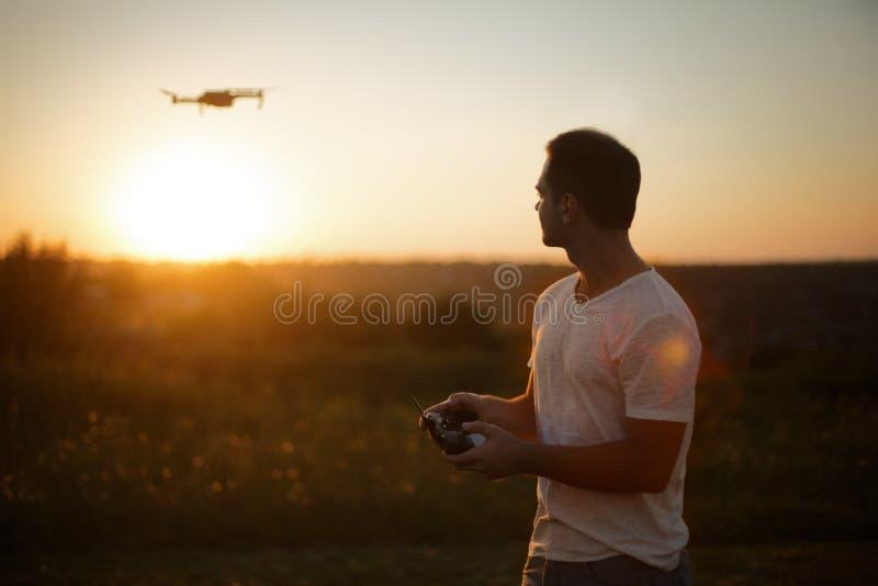 Silhouette d'un bourdon de pilotage d'homme dans le ciel avec un contrôleur à distance dans des ses mains sur le coucher du solei photographie stock libre de droits