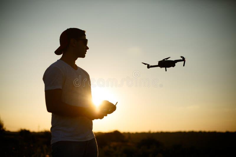 Silhouette d'un bourdon de pilotage d'homme dans le ciel avec un contrôleur à distance dans des ses mains sur le coucher du solei image libre de droits
