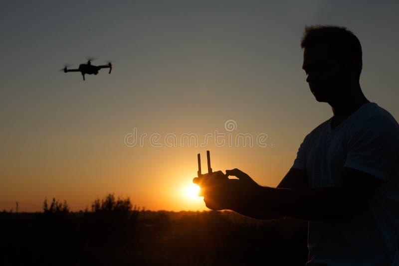 Silhouette d'un bourdon de pilotage d'homme dans le ciel avec un contrôleur à distance dans des ses mains sur le coucher du solei image stock