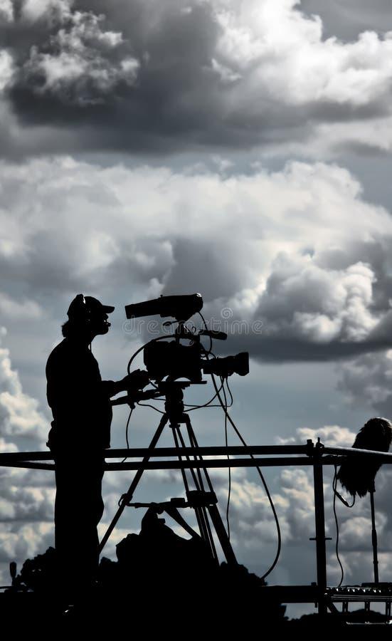 Silhouette d'un cameraman de TV contre le ciel nuageux image stock