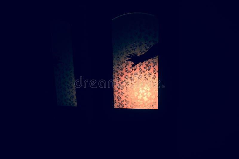Silhouette d'un chiffre inconnu d'ombre sur une porte par une porte en verre fermée La silhouette d'un humain devant une fenêtre  images libres de droits